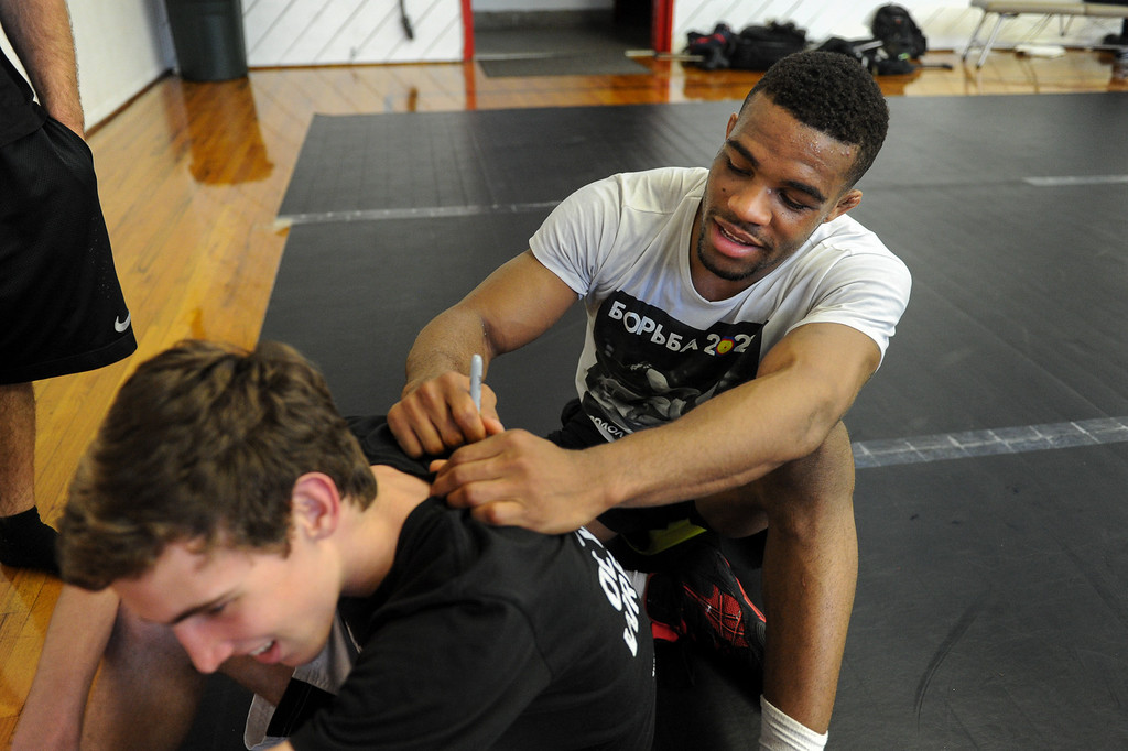 . The U.S. national wrestling team member Jordan Burroughs signs a shirt for Patrick Halkett following practice at Harvard-Westlake High School, Friday, May 17, 2013. The USA, Canada and Russia national teams will meet for in exhibition 2:00 p.m. Sunday at L.A. Memorial Sports Arena. (Michael Owen Baker/Staff Photographer)