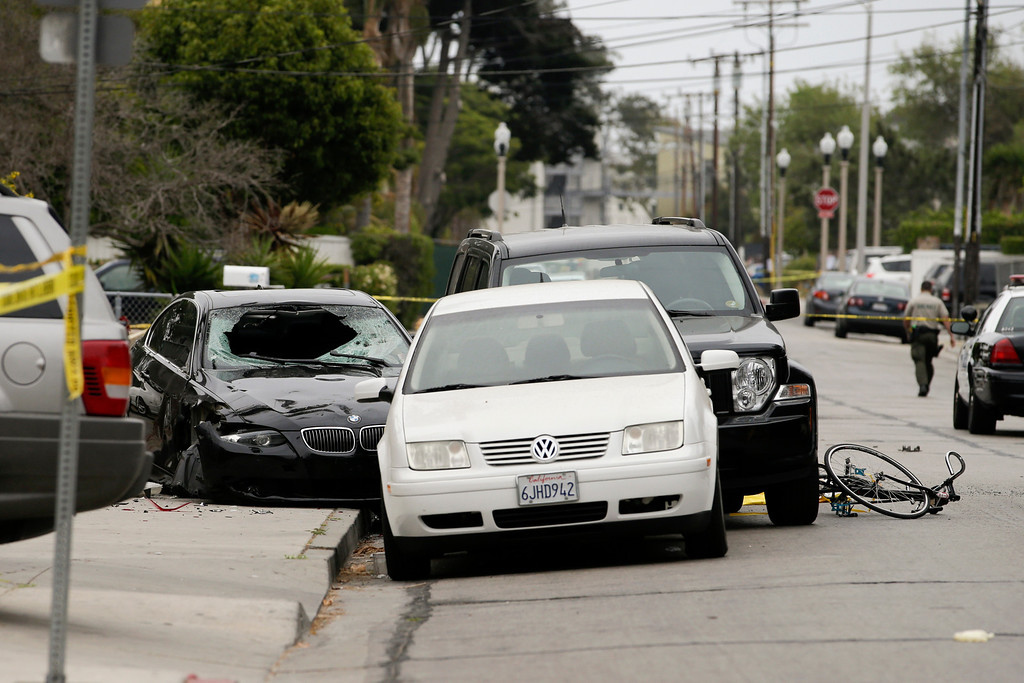 . Police tap marks of the scene where a black BMW sedan, left, driven by a drive-by shooter, rests on Saturday, May 24, 2014, in Isla Vista, Calif. The shooter went on a rampage near a Santa Barbara university campus that left seven people dead, including the attacker, and others wounded, authorities said Saturday. (AP Photo/Jae C. Hong)