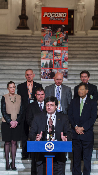 Representative Mike Carroll speaking at a press conference in the PA Capitol Rotunda on March 10, 2014. Standing Left to Right - Sen. Lisa Baker; Rep. Sid Kavulich; Brandon Igdalsky, President & CEO of Pocono Raceway; Rep. Mario Scavello; Rep. Jerry Stern; C.J. O'Donnell, Chief Marketing Officer, Hulman Sports