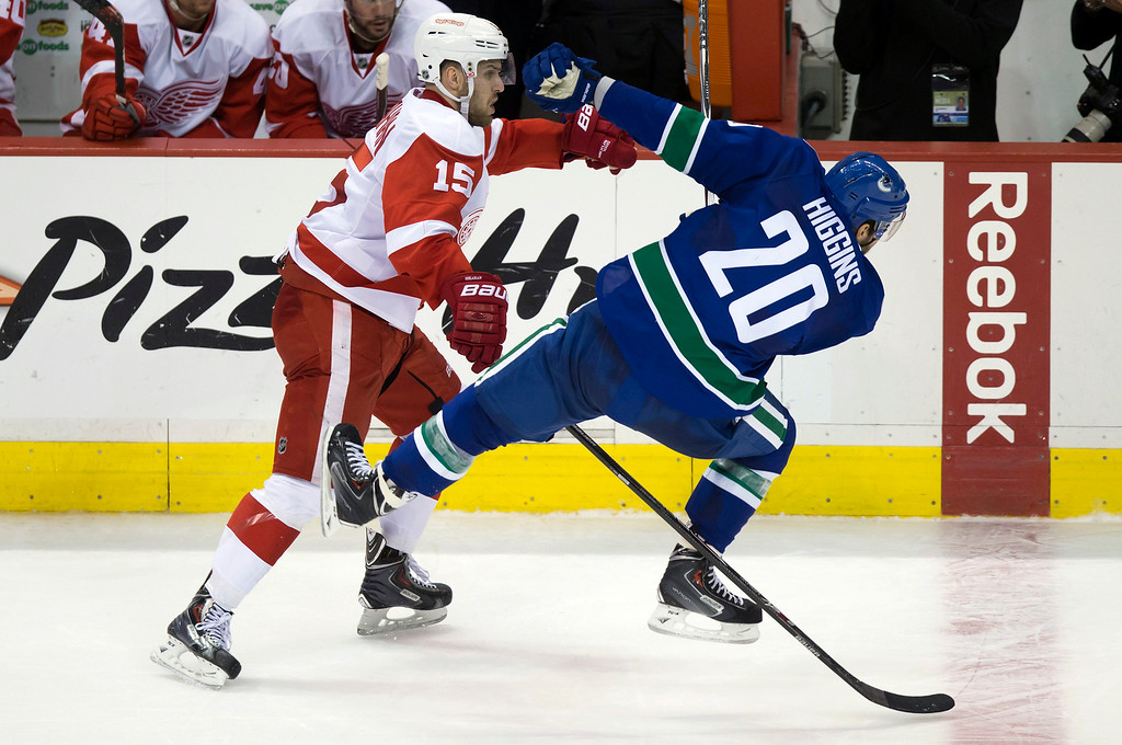 . Detroit Red Wings\' Riley Sheahan, left, checks Vancouver Canucks\' Chris Higgins during the third period of an NHL hockey game in Vancouver, British Columbia on Saturday, Jan. 3, 2015. (AP Photo/The Canadian Press, Darryl Dyck)
