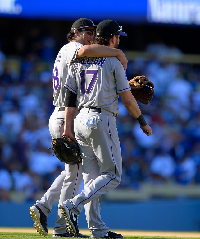 . Colorado Rockies\' Nolan Arenado, left, hugs Todd Helton after the Rockies defeated the Los Angeles Dodgers 2-1 in a baseball game, Sunday, Sept. 29, 2013, in Los Angeles. Helton was playing in the final game of his career. (AP Photo/Mark J. Terrill)