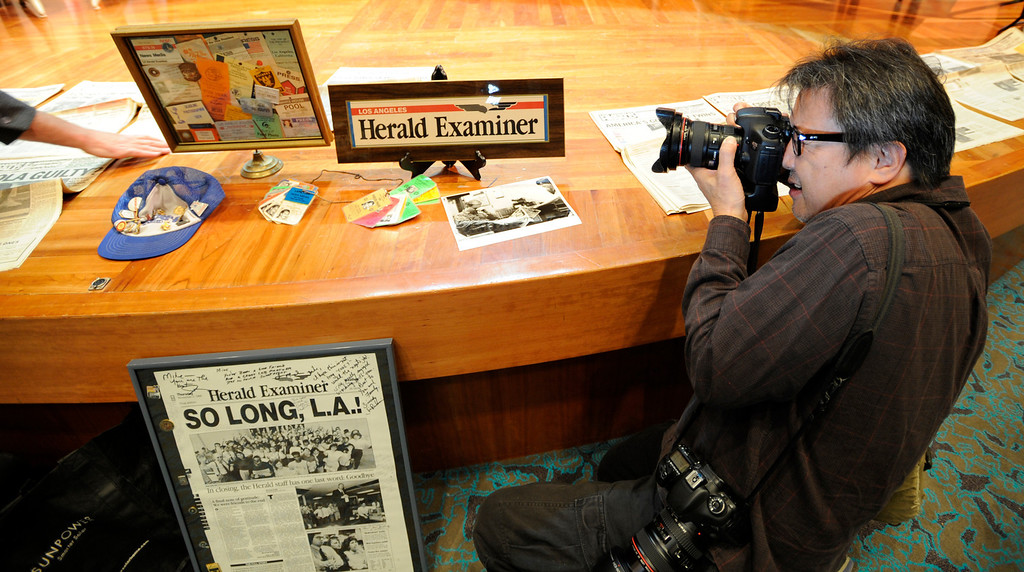 . LA Times Photographer Larry Ho takes a photo of some Herald Examiner keepsakes at the Library. Former photographers from the Los Angeles Herald Examiner gathered to take a tour of the old Herald Building, and then join for a panel discussion about their work and their days working at the old Herex. Los Angeles, CA 3/9/2013(John McCoy/Staff Photographer)