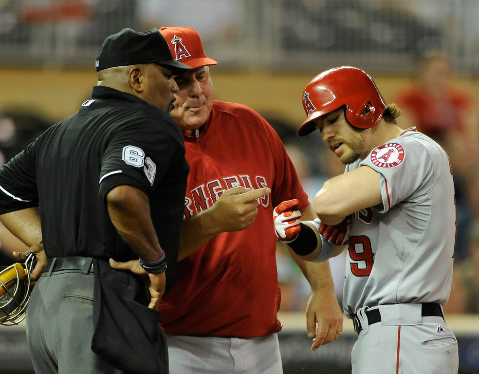. MINNEAPOLIS, MN - SEPTEMBER 9: Mike Scioscia #14 and Collin Cowgill #19 of the Los Angeles Angels of Anaheim show home plate umpire Laz Diaz #63 where they claim Cowgill was hit by a pitch during the sixth inning of the game against the Minnesota Twins on September 9, 2013 at Target Field in Minneapolis, Minnesota. (Photo by Hannah Foslien/Getty Images)