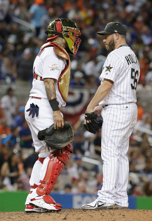 . National League\'s St. Louis Cardinals catcher Yadier Molina (4) talks to Colorado Rockies pitcher Greg Holland (56), during the eighth inning at the MLB baseball All-Star Game, Tuesday, July 11, 2017, in Miami. (AP Photo/Lynne Sladky)