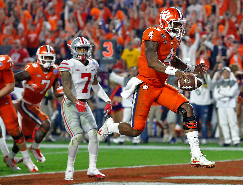 . Clemson quarterback Deshaun Watson (4) runs in for a touchdown as Ohio State safety Damon Webb (7) watches during the second half of the Fiesta Bowl NCAA college football game, Saturday, Dec. 31, 2016, in Glendale, Ariz. (AP Photo/Ross D. Franklin)