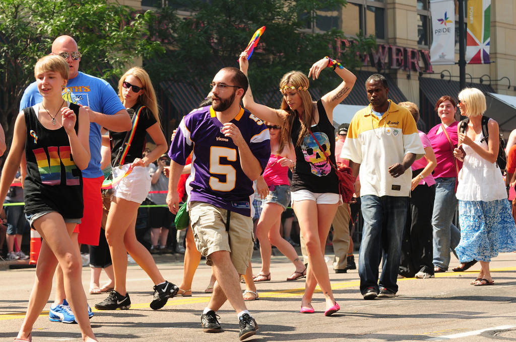 """. Matt Everhart of St. Paul wears a Chris Kluwe jersey as he does \""""the Pride Slide\"""" with other parade-goers before the start of the parade. \""""He is the perfect example of a straight ally,\"""" said Everhart about former Vikings punter Chris Kluwe, who was the parade\'s grand marshal. (Pioneer Press: Scott Takushi)"""