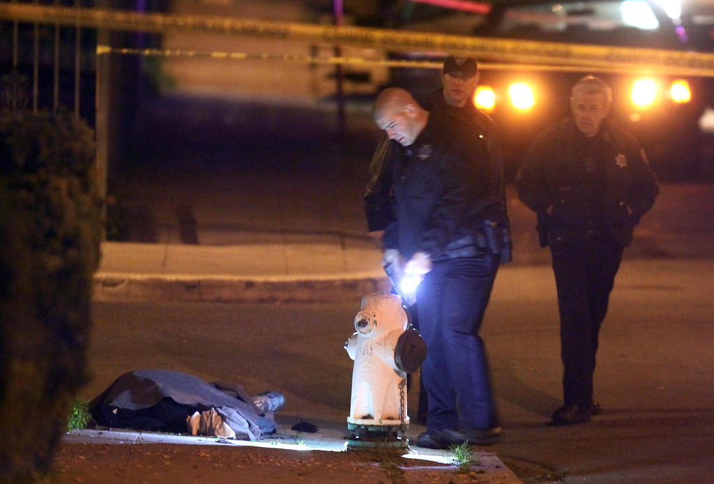 . The dead body of unidentified man who was gunned down lies covered on the ground as Oakland police officers investigate the crime scene at the corner of 94th Avenue and Hillside Street in Oakland, Calif., on Friday, Jan. 11, 2013. It was the fourth homicide of the day and the sixth of the week. (Ray Chavez/Staff)