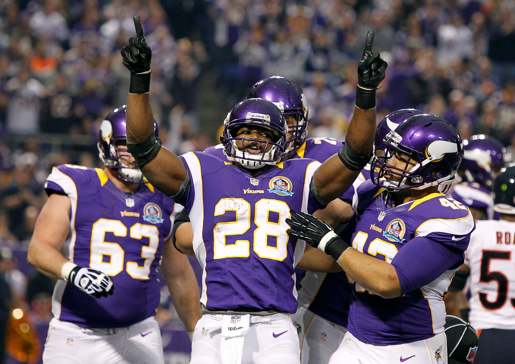 . Minnesota Vikings running back Adrian Peterson (28) celebrates with teammate Jerome Felton, right, after scoring on a 1-yard touchdown run during the first half of an NFL football game against the Chicago Bears Sunday, Dec. 9, 2012, in Minneapolis. (AP Photo/Genevieve Ross)