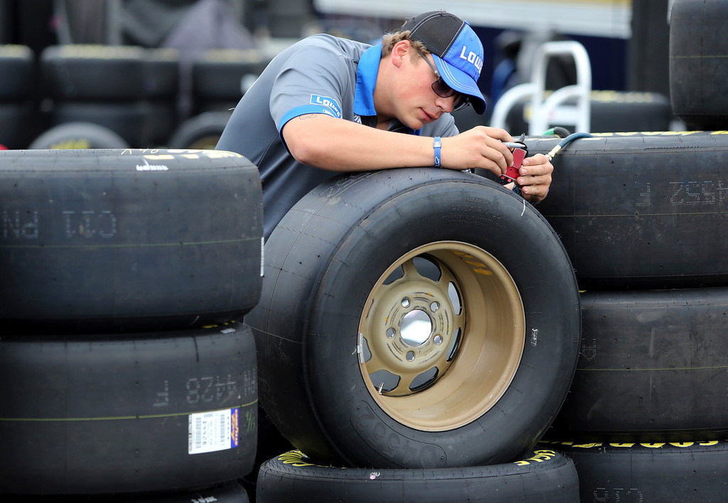 . Will Goodnow checks tires for Jimmie Johnson\'s car before practice for Saturday\'s NASCAR Sprint Cup series auto race at Charlotte Motor Speedway in Concord, N.C., Friday, Oct. 11, 2013. (AP Photo/Bob Jordan)