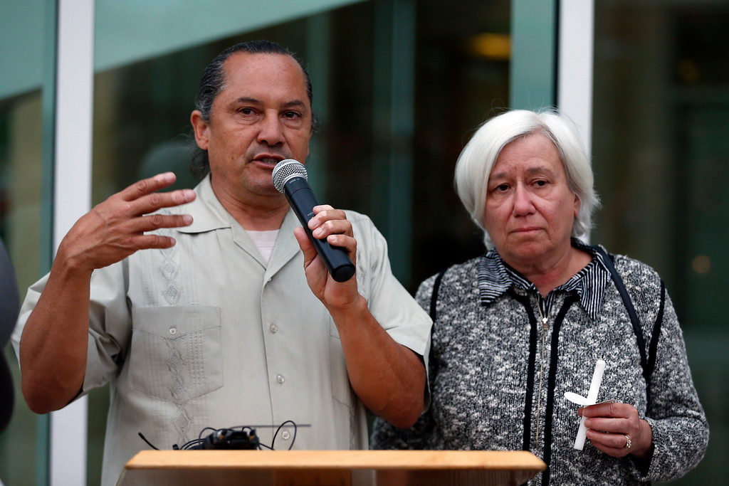 . Organizer and Day Labor Center Executive Director Gabriel Hernandez, left, speaks as Hayward Mayor Barbara Halliday waits for her turn during a candlelight vigil for slain Hayward police Sgt. Scott Lunger at Hayward City Hall in Hayward, Calif., on Wednesday, July 22, 2015. Hernandez knew Lunger, who was killed during a traffic stop early Wednesday. (Ray Chavez/Bay Area News Group)