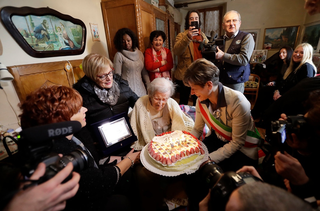 . Verbania\'s  Mayor Silvia Marchionini, right,  presents Emma Morano with a cake in the day of her 117th birthday in Verbania, Italy, Tuesday, Nov. 29, 2016.  At 117 years of age, Emma is now the oldest person in the world and is believed to be the last surviving person in the world who was born in the 1800s, coming into the world on Nov. 29, 1899. (AP Photo/Antonio Calanni)