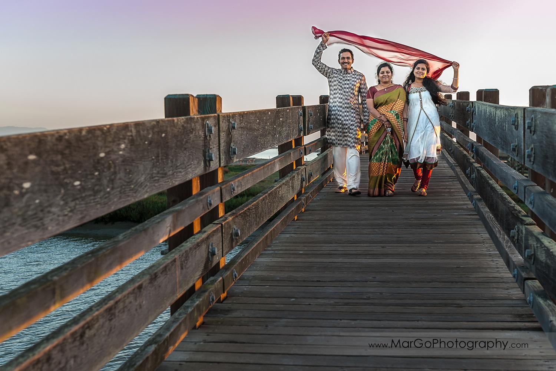 Indian family walking on the woood bridge at Don Edwards Refuge in Fremont