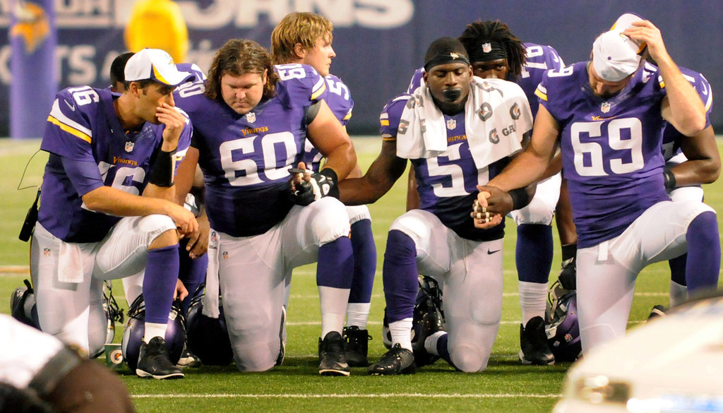 . Vikings players (from left) Matt Cassel , left to right, Jeff Baca, Larry Dean  and Jared Allen kneel as they watch teammate Seth Olsen being taken off the field after a neck injury during the second quarter.  (Pioneer Press: Sherri LaRose-Chiglo)