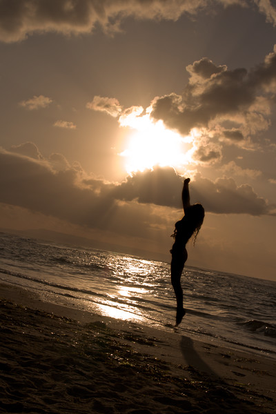 Girl jumping on sunrise at the beach
