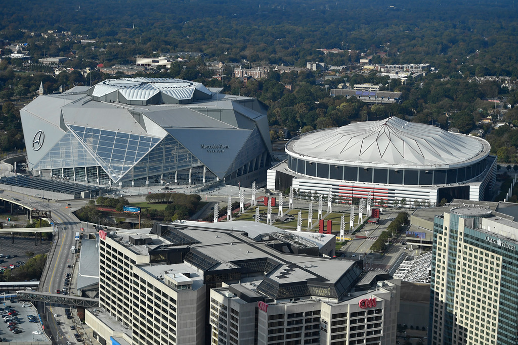 . FILE- In this Nov. 1, 2017, file photo, the Georgia Dome is seen at right with the Mercedes-Benz stadium at left in Atlanta. The Georgia Dome is scheduled to be imploded Monday, Nov. 20. The dome was not only the former home of the Atlanta Falcons but also the site of two Super Bowls, 1996 Olympics Games events and NCAA basketball tournaments among other major events. (AP Photo/Mike Stewart, File)