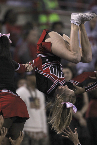 Cheerleader, Cameron Puckett, flips upside down during a pyramid stunt