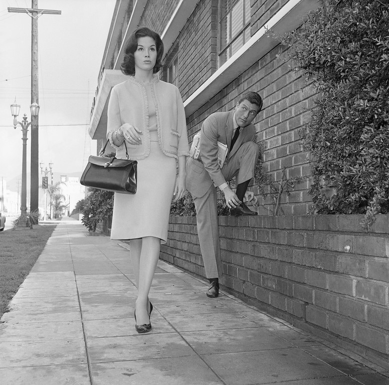 . Actor Dick Van Dyke, right, looks on as actress Mary Tyler Moore walks by, Feb. 22, 1962, Los Angeles, Calif. (AP Photo/Don Brinn)
