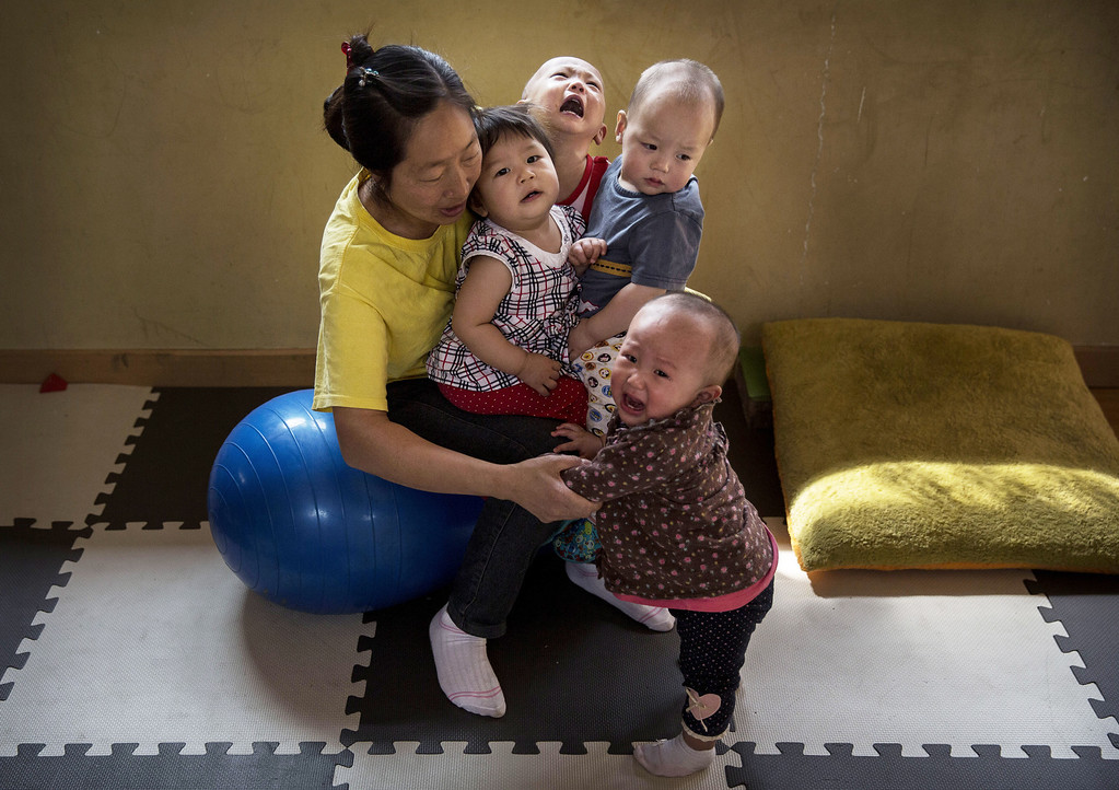 . A Chinese care worker holds children on her lap as she cares for them at a foster care center on April 2, 2014 in Beijing, China.  (Photo by Kevin Frayer/Getty Images)