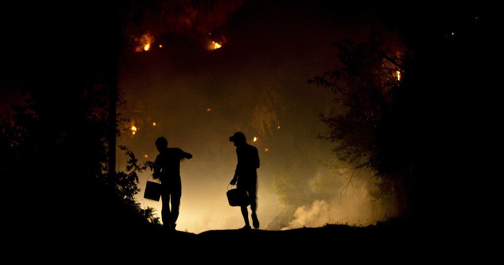 . Two men carry buckets to try to extinguish a wildfire approaching houses in Santiago de Besteiros, near Caramulo, central Portugal, early on August 30, 2013.    AFP PHOTO / PATRICIA DE MELO MOREIRA/AFP/Getty Images
