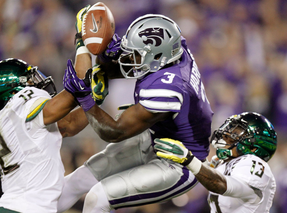 Description of . Kansas State wide receiver Chris Harper (3) cannot handle a pass as Oregon's Brian Jackson (12) and Troy Hill (13) defend during the first half of the Fiesta Bowl NCAA college football game, Thursday, Jan. 3, 2013, in Glendale, Ariz. (AP Photo/Paul Connors)