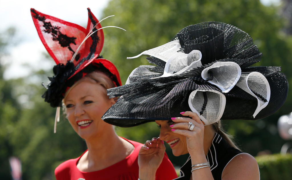 . Race goers hang onto their hats in a gusty wind as they arrive on the first day of the Royal Ascot horse racing meeting at Ascot, England, Tuesday, June, 17, 2014.  (AP Photo/Alastair Grant)