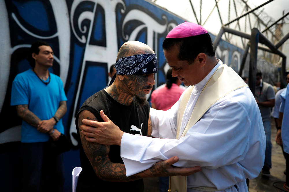 Description of . Catholic priest Fabio Colindres (L) speaks with a member of Mara Salvatrucha gang during a mass at the prison of Ciudad Barrios, 160 km east of San Salvador, El Salvador on June 19, 2012. Inmates participated in a mass to celebrate 100 days after a truce was declared between gangs and the Salvadorean goverment.  AFP PHOTO/ Jose CABEZAS/AFP/Getty Images