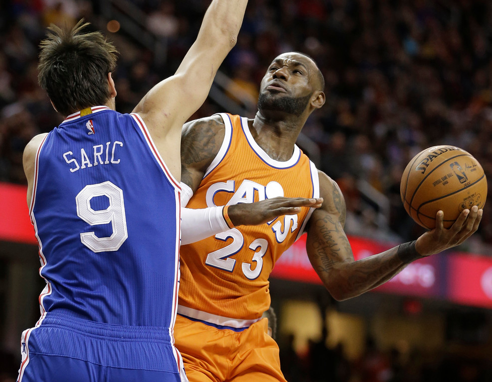 . Cleveland Cavaliers\' LeBron James (23) drives to the basket against Philadelphia 76ers\' Dario Saric (9), from Croatia, in the first half of an NBA basketball game, Friday, March 31, 2017, in Cleveland. (AP Photo/Tony Dejak)