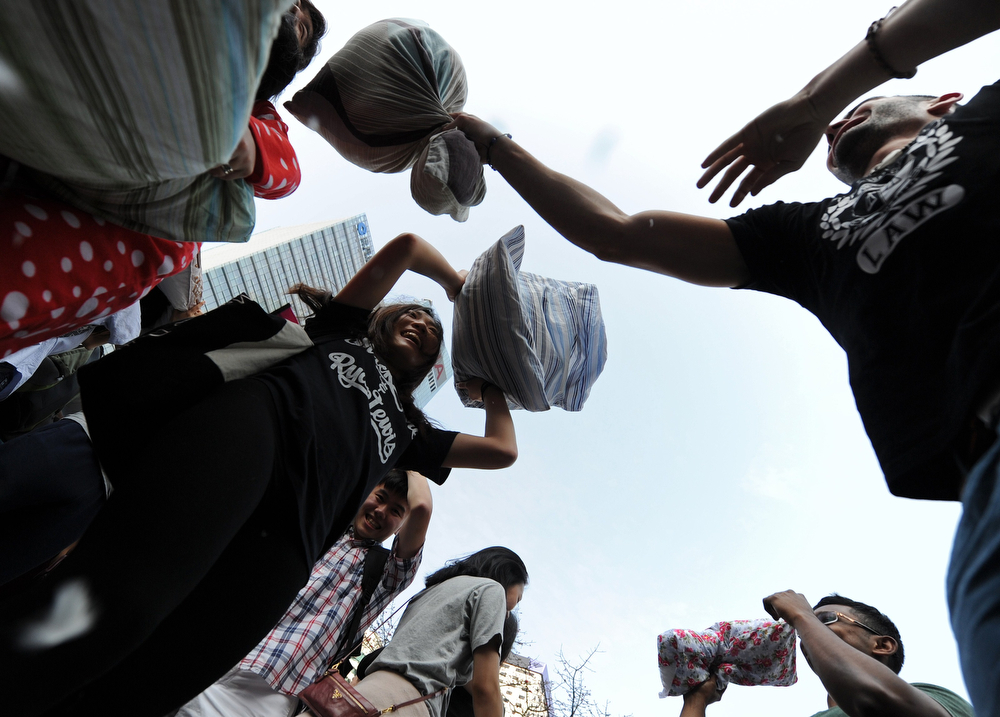 Description of . People hit each other with pillows during the fourth international pillow fight day in Hong Kong on April 5, 2014. Some two hundred people formed a sea of pillows and loose feathers as they went at each other while wearing a colourful assortment of pajamas. (DALE de la REY/AFP/Getty Images)