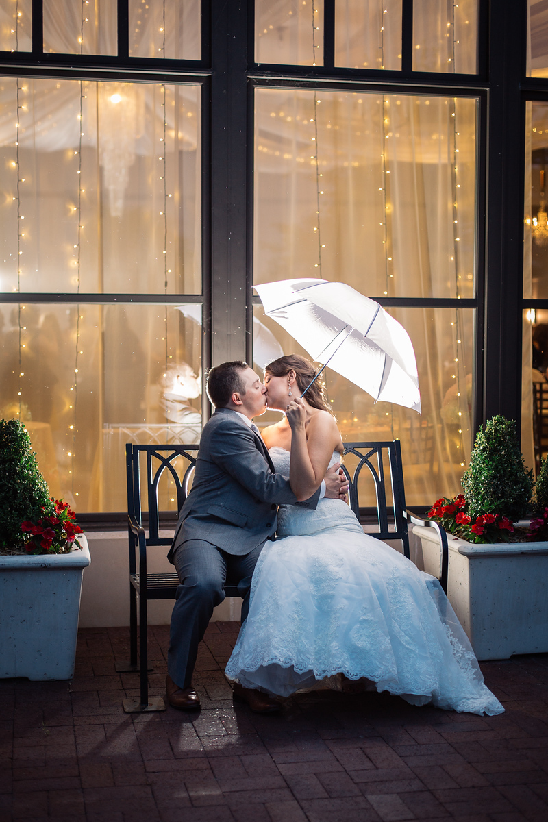 newlyweds share kiss under umbrella