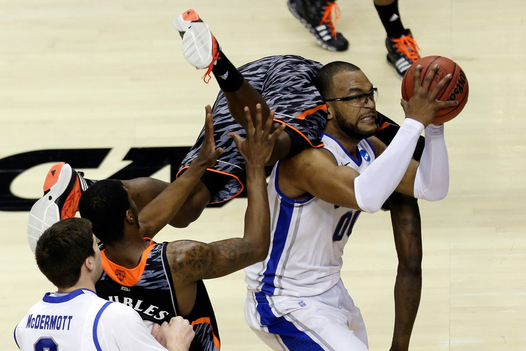 . Cincinnati\'s Justin Jackson, top, falls over Creighton\'s Gregory Echenique during the second half of a second-round game of the NCAA college basketball tournament, Friday, March 22, 2013, in Philadelphia. Creighton won 67-63. (AP Photo/Matt Rourke)
