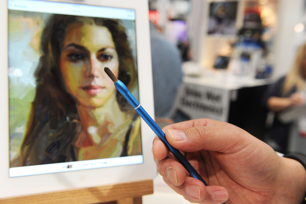 ". A NomadBrush Flex paintbrush stylus is displayed in front of an iPad ""oil\"" painting by artist Rick Graham at the 2014 International CES in Las Vegas, Nevada, January 8, 2014.  Each bristle of the paintbrush stylus, which was recently released and is priced at USD $29, is conductive. AFP PHOTO / Robyn Beck/AFP/Getty Images"