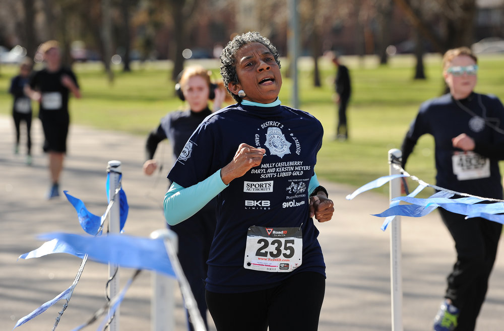 """. Former city council woman Allegra \""""Happy\"""" Haynes finishes the race.  Family, colleagues, and friends of slain Denver Police Officer Celena Hollis turned out April 7, 2013 for a 5k run and walk to raise money for a scholarship fun and a memorial bench in City Park in Denver, CO.  Over 300 runners and walkers participated in the race that started at 9:00 am.  The race looped around City Park.  After the race, a gathering was held to remember Hollis and 22 white doves were released in her memory.  (Photo By Helen H. Richardson/ The Denver Post)"""