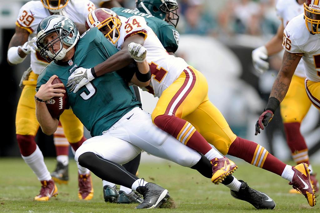 . Philadelphia Eagles quarterback Nick Foles is sacked by Washington Redskins defensive back Trenton Robinson during the first half of an NFL football game in Philadelphia, Sunday, Nov. 17, 2013. (AP Photo/Michael Perez)