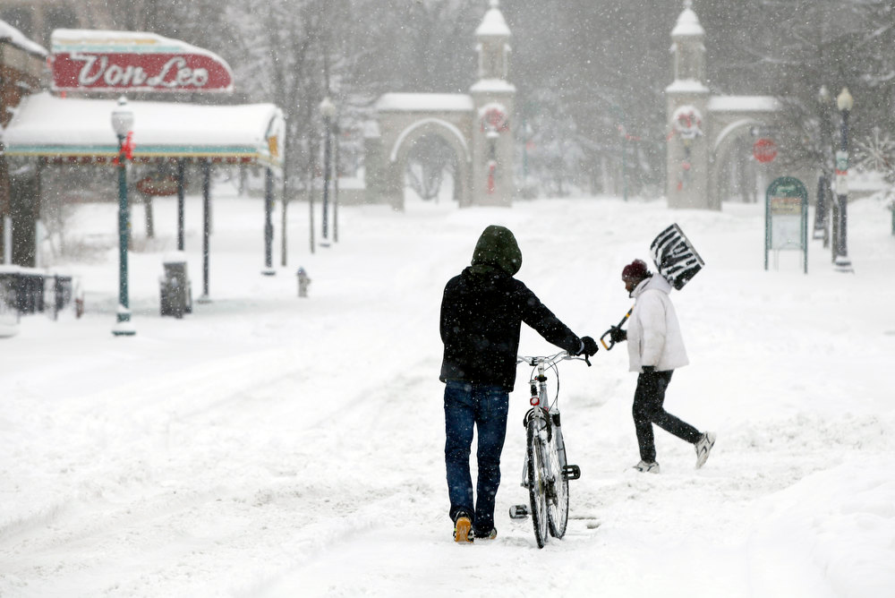 Description of . Heading toward Indiana University's Sample Gates, Yasukiko Aoliki, left, heads home after trekking downtown for a haircut only to find the business closed, Wednesday, Dec. 26, 2012 in Bloomington, Ind.  (AP Photo/Bloomington Herald-Times, Jeremy Hogan)