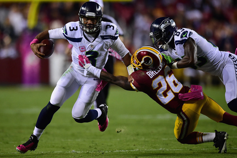 . Quarterback Russell Wilson #3 of the Seattle Seahawks stiff arms strong safety Bashaud Breeland #26 of the Washington Redskins in the first quarter of a game at FedExField on October 6, 2014 in Landover, Maryland.  (Photo by Patrick Smith/Getty Images)