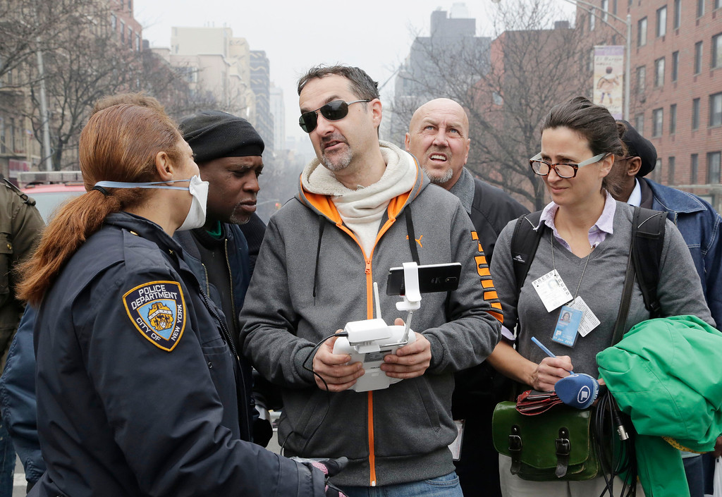 . A New York City police officer, left, tells Brian Wilson, center, to land the drone that he was flying over the scene of an explosion that leveled two apartment buildings in East Harlem, Wednesday, March 12, 2014 in New York. Wilson says he uses the aerial drone to document buildings, weddings and news events. (AP Photo/Mark Lennihan)