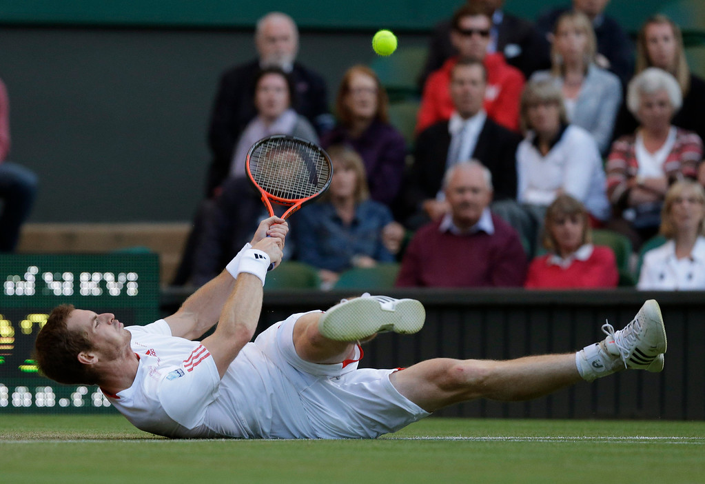 . In this June 30, 2012 file photo, Andy Murray of Britain struggles to try and return a shot to Marcos Baghdatis of Cyprus during a third round men\'s singles match at the All England Lawn Tennis Championships at Wimbledon, England. (AP Photo/Anja Niedringhaus, File)