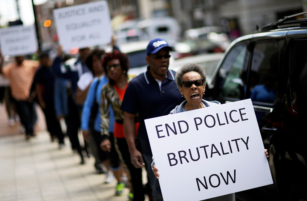 . Protestors demonstrate outside the State Attorney\'s office calling for the continued investigation into the death of Freddie Gray, Wednesday, April 29, 2015, in Baltimore. Activists stressed that they will continue to press for answers in the case of Gray, the 25-year-old black man whose death from a spinal-cord injury under mysterious circumstances while in police custody set off the riots.  (AP Photo/David Goldman)