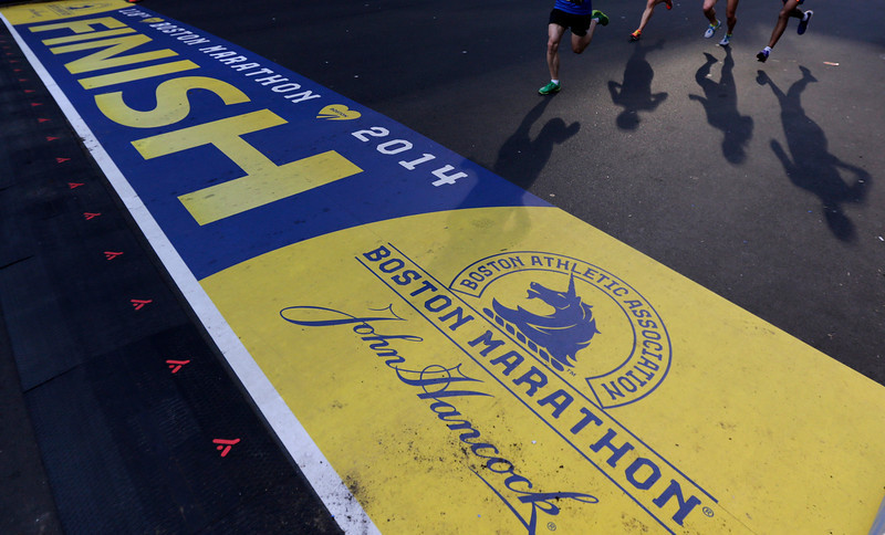 . Runners approach the finish line of the Boston Marathon, a midpoint of a 5K race, on Boston Marathon weekend, Saturday, April 19, 2014 in Boston. The 118th Boston Marathon is scheduled to run on Patriots Day, Monday, April 21. (AP Photo/Charles Krupa)