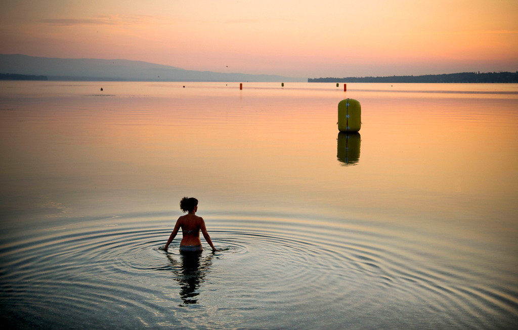 . In this Sunday, July 21, 2013 file photo made by Associated Press photographer Anja Niedringhaus, a woman takes a dip in Lake Geneva at sunrise in Geneva, Switzerland.  (AP Photo/Anja Niedringhaus, File)