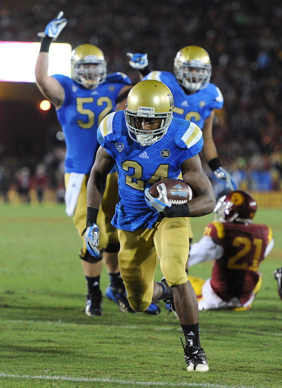 . UCLA #24 Paul Perkins scores a touchdown late in the 4th quarter. UCLA defeated USC 35 to 14 in a matchup of cross town rivals at the Los Angeles Memorial Coliseum in Los Angeles, CA.  photo by (John McCoy/Los Angeles Daily News)