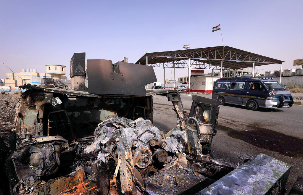 . A vehicle drives past the burnt out remains of an Iraqi army vehicle seen at the Kukjali Iraqi Army checkpoint, some 10km of east of the northern city of Mosul, on June 11, 2014, the day after Sunni militants, including fighters from the Islamic State of Iraq and the Levant (ISIL) overran the city.  Half a million people were estimated to have fled Iraq\'s second largest city, as Islamist militants tightened their grip after overrunning it and a swathe of other territory, patrolling its streets and calling for government employees to return to work. SAFIN HAMED/AFP/Getty Images
