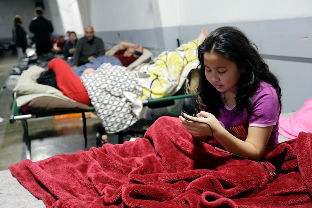 . Bea Noelle De Leon, 11, of Oroville, Calif., checks her phone at a shelter for evacuees from cities surrounding the Oroville Dam, Monday, Feb. 13, 2017, in Chico, Calif. The thousands of people who were ordered to leave their homes after a damaged California spillway threatened to unleash a 30-foot wall of water may not be able to return until significant erosion is repaired, authorities said Monday. (AP Photo/Marcio Jose Sanchez)