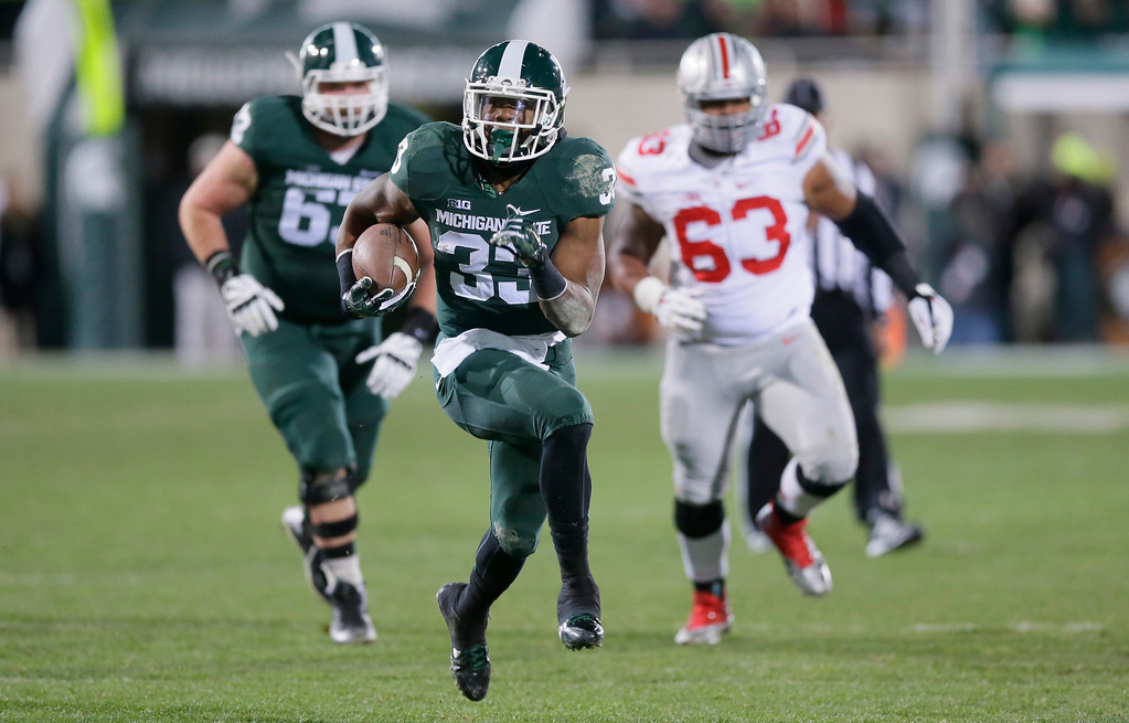 . Michigan State running back Jeremy Langford (33) outruns the Ohio State defense for a 33-yard touchdown during the first half of an NCAA college football game in East Lansing, Mich., Saturday, Nov. 8, 2014. (AP Photo/Carlos Osorio)