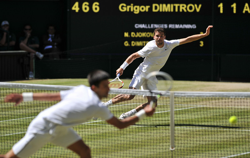 . Bulgaria\'s Grigor Dimitrov (back) hits a ball that passes Serbia\'s Novak Djokovic at the net during their men\'s singles semi-final match on day 11 of  the 2014 Wimbledon Championships at The All England Tennis Club in Wimbledon, southwest London, on July 4, 2014. (GLYN KIRK/AFP/Getty Images)