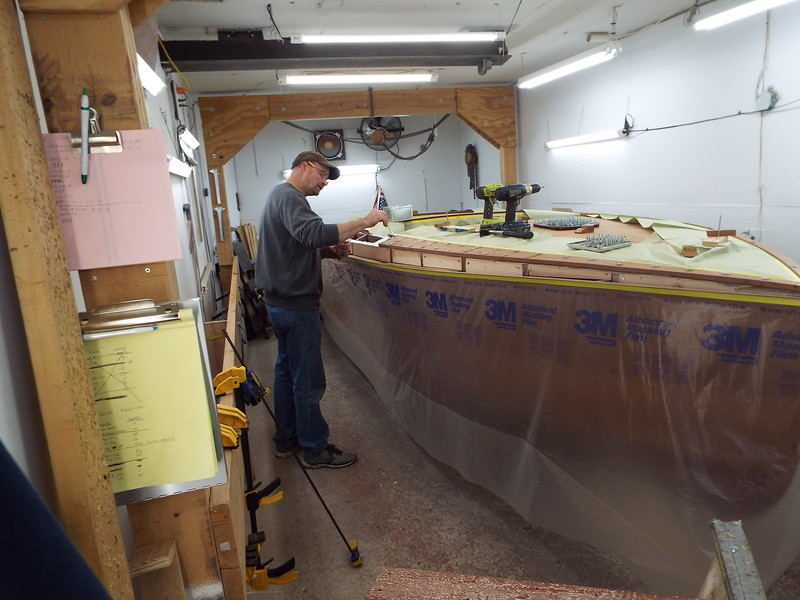 Applying epoxy on the boat before installing the cover board.