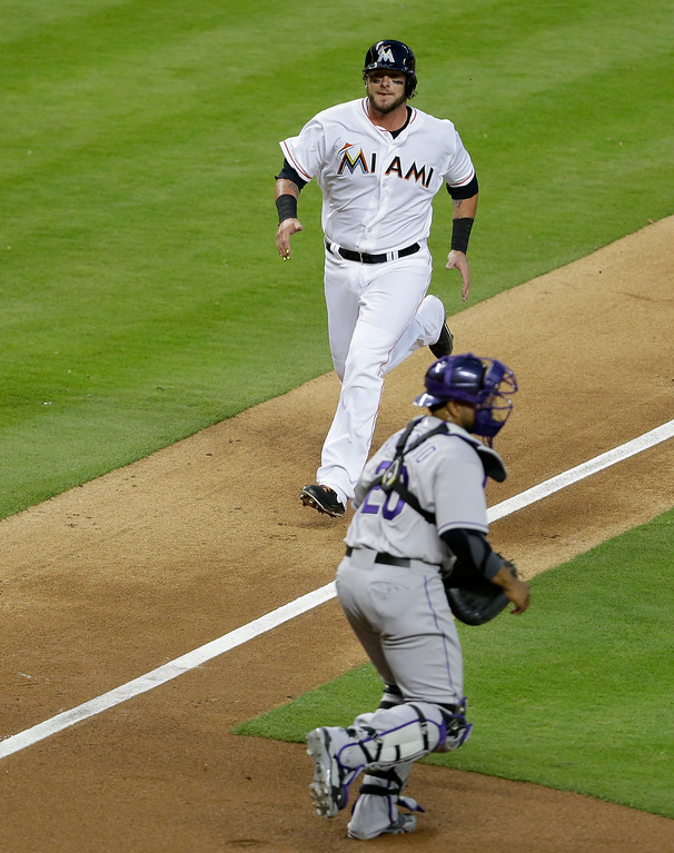 . Miami Marlins\' Jarrod Saltalamacchia, left, runs home to score on a sacrifice fly by Adeiny Hechavarria as Colorado Rockies catcher Wilin Rosario waits for the throw in third inning of a baseball game, Tuesday, April 1, 2014, in Miami. The Marlins defeated the Rockies 4-3. (AP Photo/Lynne Sladky)