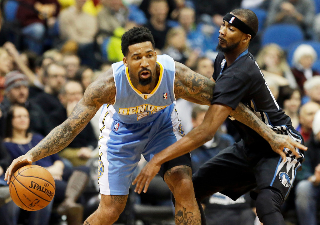 . Denver Nuggets\'s Wilson Chandler, left, keeps the ball away from Minnesota Timberwolves\' Corey Brewer in the first quarter of an NBA basketball game on Wednesday, Nov. 27, 2013, in Minneapolis. (AP Photo/Jim Mone)