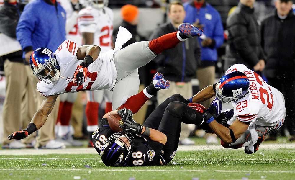 . Baltimore Ravens tight end Dennis Pitta, center, makes a catch between New York Giants strong safety Stevie Brown, left, and cornerback Corey Webster in the second half of an NFL football game in Baltimore, Sunday, Dec. 23, 2012. (AP Photo/Nick Wass)