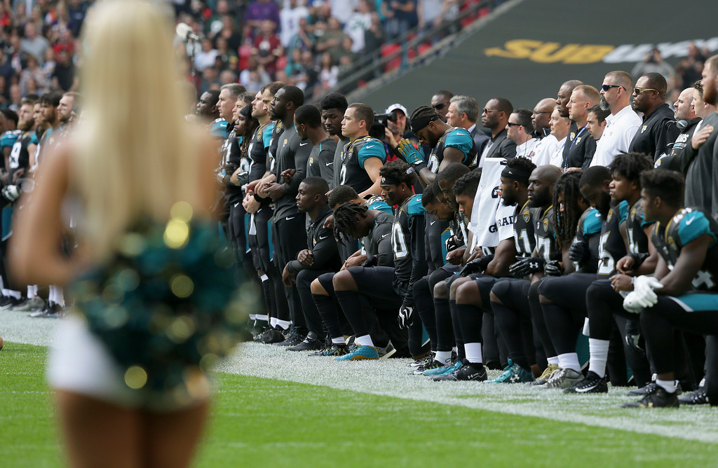 . Jacksonville Jaguars players kneel down during the playing of the U.S. national anthem before an NFL football game against the Baltimore Ravens at Wembley Stadium in London, Sunday Sept. 24, 2017. (AP Photo/Tim Ireland)